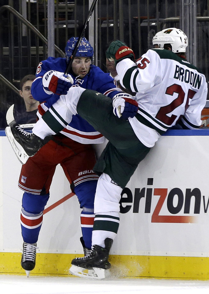 New York Rangers' Derick Brassard, left, checks Minnesota Wild's Jonas Brodin during the second period of an NHL hockey game, Sunday, Dec. 22, 2013, in New York. (AP Photo/Seth Wenig)