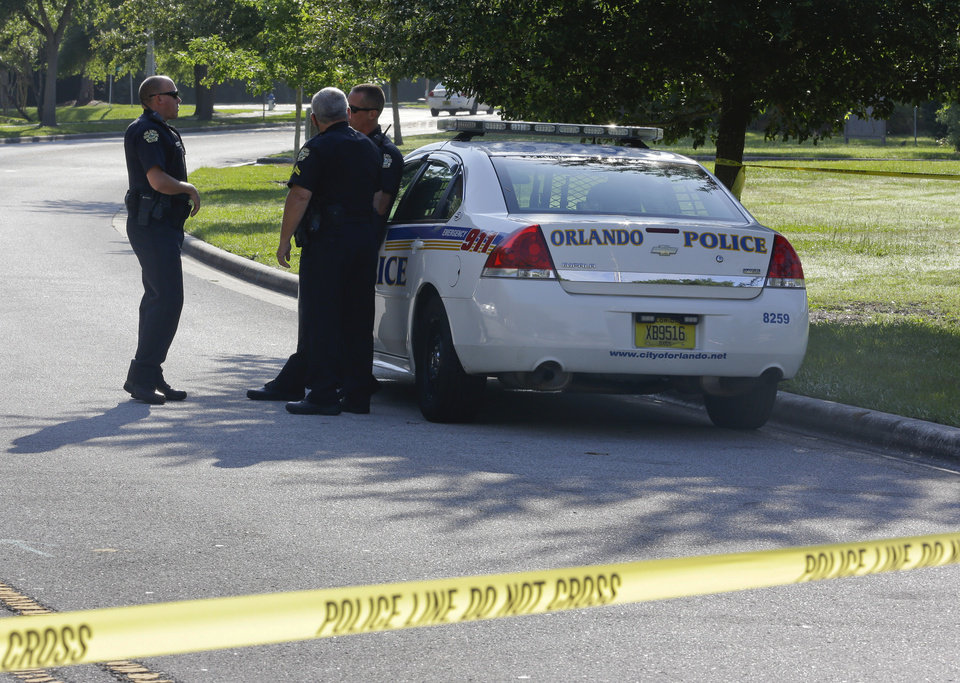 Photo - Police officers block the entrance to an apartment complex where man was fatally shot, Wednesday, May 22, 2013, in Orlando, Fla. The FBI says the man, being questioned by authorities in the Boston bombing probe, was fatally shot when he initiated a violent confrontation. (AP Photo/John Raoux)
