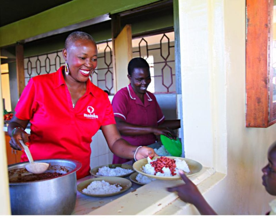 Photo - Maisha Project Executive Director Beatrice Williamson helps feed sponsored children in Kenya. [PHOTO PROVIDED]