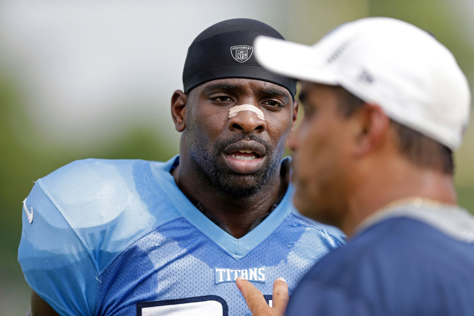 Photo - Tennessee Titans strong safety Bernard Pollard, left, listens to assistant secondary coach Steve Brown during NFL football training camp Wednesday, July 31, 2013, in Nashville, Tenn. The Titans signed Pollard as a free agent after Pollard won the Super Bowl with the Baltimore Ravens, and are hoping Pollard can help lead a defense bouncing back from a horrible season. (AP Photo/Mark Humphrey)