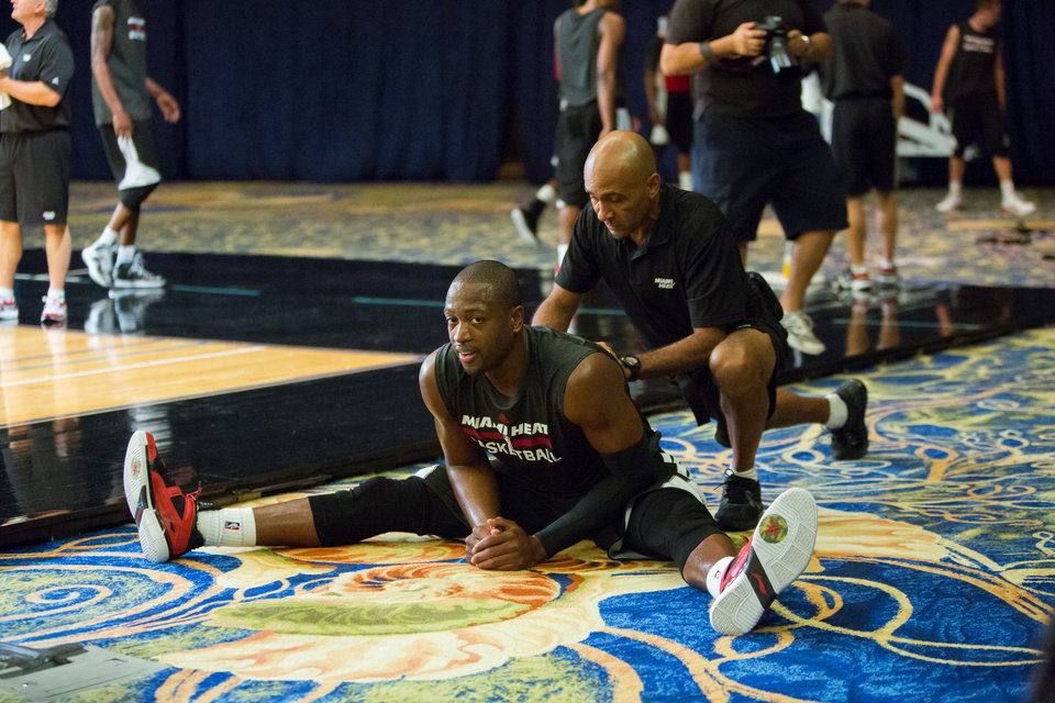 Photo - Miami Heat point guard Dwayne Wade stretches during a training camp session at the Atlantis Resort in Paradise Island, Bahamas, Tuesday, Oct. 1, 2013. The two-time defending NBA champions opened training camp Tuesday at the resort, with two practices scheduled for opening day. (AP Photo/Bahamas Visual Services, Dante Carrer)