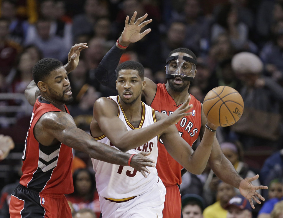 Photo - Toronto Raptors' Amir Johnson, left, and Patrick Patterson, right, put pressure on Cleveland Cavaliers' Tristan Thompson, from Canada, during the first quarter of an NBA basketball game, Tuesday, Feb. 25, 2014, in Cleveland. (AP Photo/Tony Dejak)