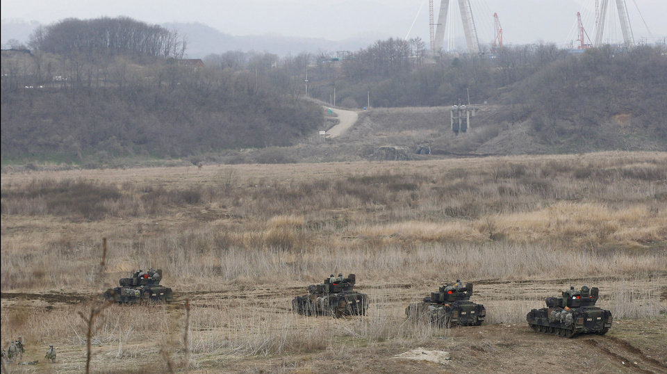 Photo - U.S. Army soldiers drive armored vehicles during annual military drills in Yeoncheon, South Korea, near the border with North Korea, Tuesday, April 9, 2013. North Korea has unleashed a flurry of war threats and provocations over U.N. sanctions for its last nuclear test, and over the ongoing U.S.-South Korean military drills, which the allies say are routine but Pyongyang says is a preparation for a northward invasion. (AP Photo/Ahn Young-joon)