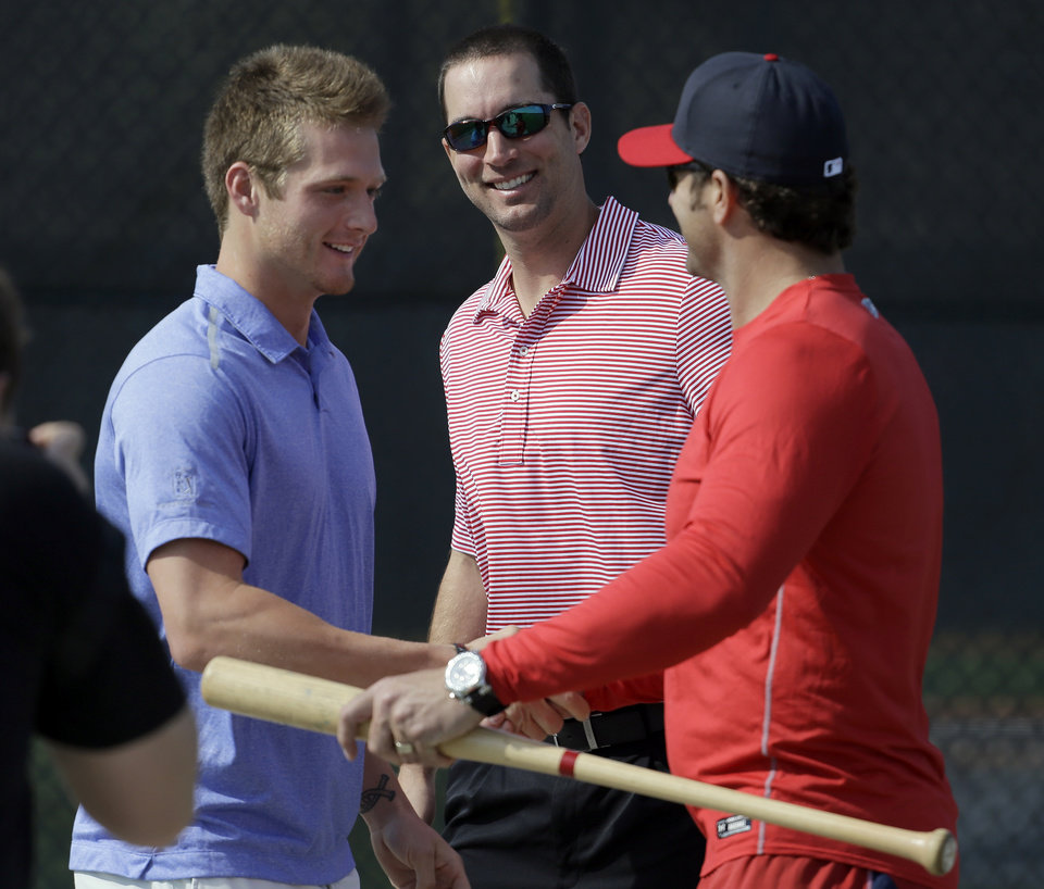 Photo - St. Louis Cardinals pitchers Shelby Miller, left, and Adam Wainwright, center, greet manager Mike Matheny after arriving at the Cardinals' spring training baseball practice facility Wednesday, Feb. 12, 2014, in Jupiter, Fla. Cardinals pitchers and catchers first official practice is scheduled for Thursday. (AP Photo/Jeff Roberson)