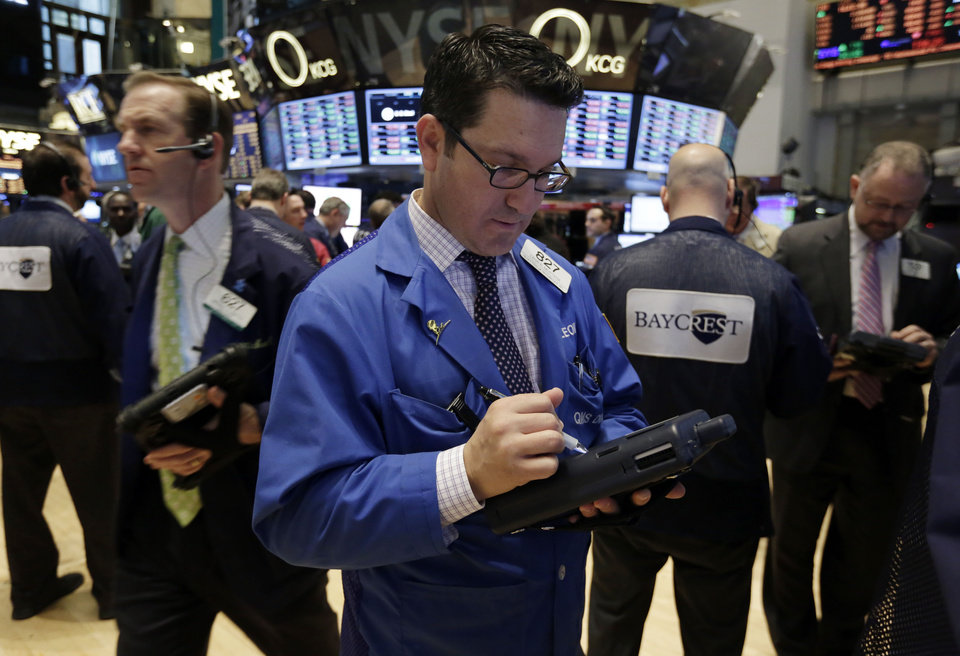 Photo - Trader Leon Montana, center, works on the floor of the New York Stock Exchange Wednesday, March 19, 2014. Stocks are slightly lower in early trading on Wall Street as traders wait for the latest policy decision from the Federal Reserve. (AP Photo/Richard Drew)