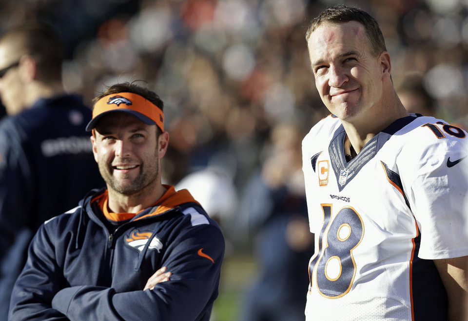 Photo - Denver Broncos quarterback Peyton Manning (18) stands on the sideline with wide receiver Wes Welker during the second half of an NFL football game against the Oakland Raiders, Sunday, Dec. 29, 2013, in Oakland, Calif. (AP Photo/Marcio Jose Sanchez)