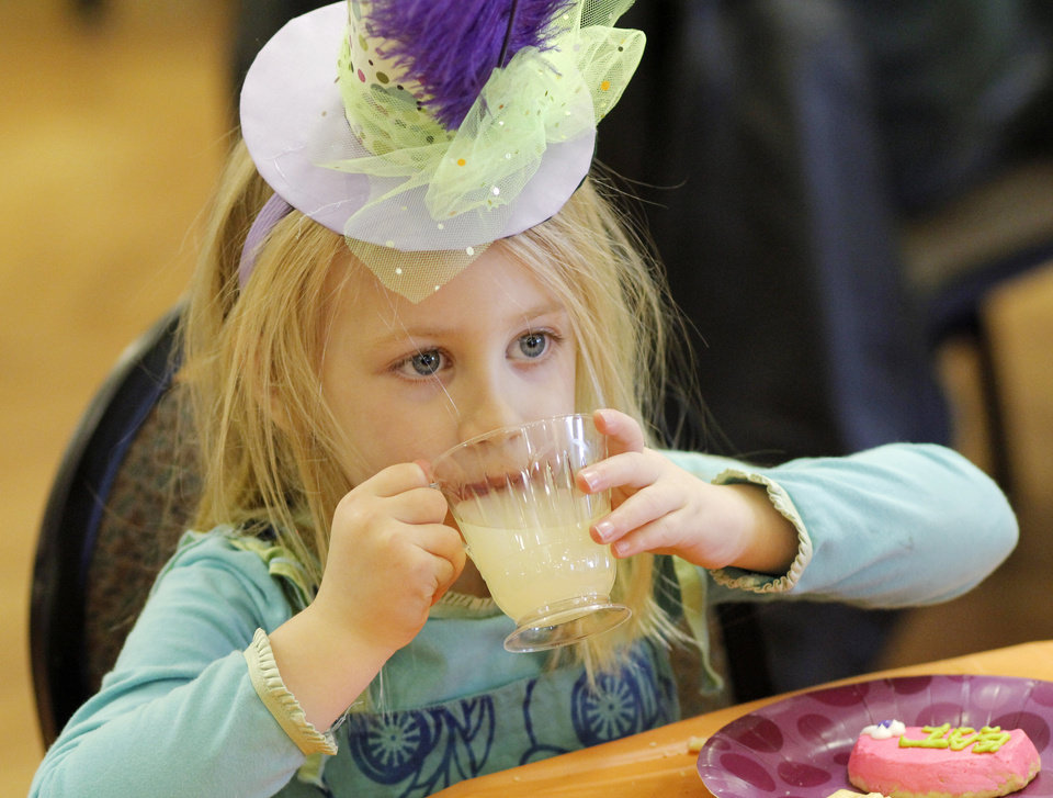 Photo - Olivia Snyder, 5, eats at the Daddy-Daughter Mad Hatter Tea Party at the Edmond Multi-purpose Community Center Sunday, Feb. 12, 2012. Olivia's twin sister Hannah was also at the party. Photo by Doug Hoke, The Oklahoman ORG XMIT: OKC1202091803570754