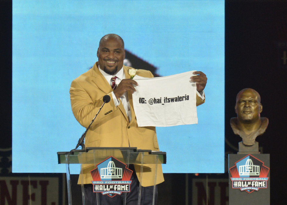 Photo - Hall of Fame inductee Walter Jones holds up a towel with his daughter's Instagram address during the Pro Football Hall of Fame enshrinement ceremony Saturday, Aug. 2, 2014, in Canton, Ohio. (AP Photo/David Richard)
