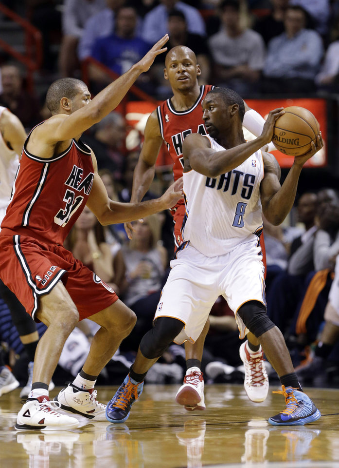 Charlotte Bobcats guard Ben Gordon (8) looks for an opening past Miami Heat forward Shane Battier (31) and guard Ray Allen, rear, during the first half of an NBA basketball game, Monday, Feb. 4, 2013 in Miami. (AP Photo/Wilfredo Lee)