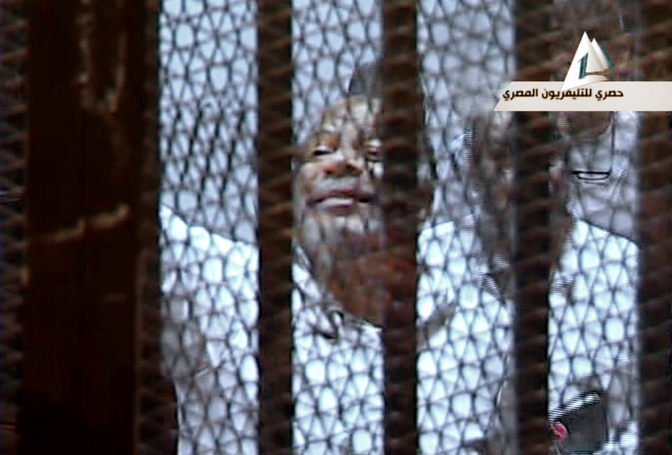 Photo - In this image taken from Egypt State TV,  Muslim Brotherhood lawmaker Saad el-Katatni waves from the defendant's cage in a courtroom in Cairo, Egypt, Tuesday, Jan. 28. 2014. Egypt's toppled President Mohammed Morsi stood inside a glass-encased metal cage on Tuesday, separated from other defendants for the start of a new trial Tuesday over charges from prison breaks during the country's 2011 revolution, state television reported. (AP Photo/Egyptian State TV)
