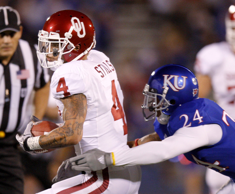 Photo - Oklahoma's Kenny Stills (4) runs past Kansas' Bradley McDougald (24) after a reception during the college football game between the University of Oklahoma Sooners (OU) and the University of Kansas Jayhawks (KU) at Memorial Stadium in Lawrence, Kansas, Saturday, Oct. 15, 2011. Photo by Bryan Terry, The Oklahoman