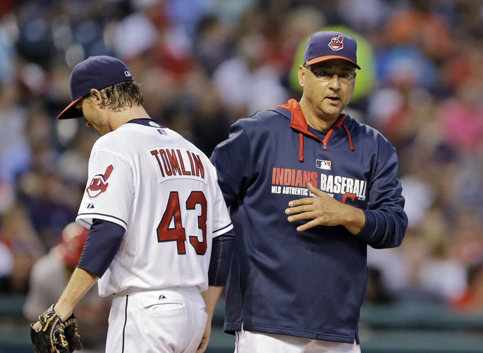 Photo - Cleveland Indians manager Terry Francona removes starting pitcher Josh Tomlin (43) from a baseball game against the Cincinnati Reds in the fifth inning Tuesday, Aug. 5, 2014, in Cleveland. (AP Photo/Mark Duncan)