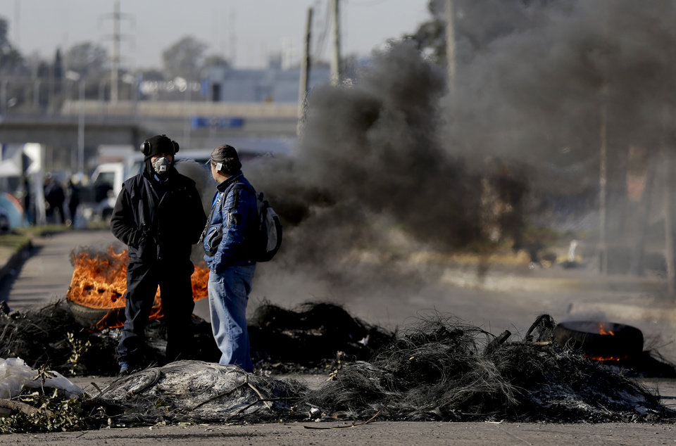 Photo - Two men stand next to a barricade of burning tires, meant as a supportive gesture to fellow workers who continue to work despite being laid off, outside the entrance of the R.R. Donnelley & Sons printing plant, on the outskirts of Buenos Aires, Argentina, Thursday, Aug. 14, 2014. About 200 workers decided to keep working until union leaders, in talks with the Labor Ministry, find a solution to reverse the plant layoffs. (AP Photo/Natacha Pisarenko)
