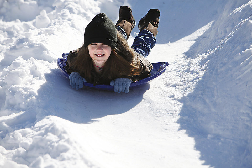 Photo - Right: Rachel McCarty, 8, slides on the snow in her front yard in Edmond.