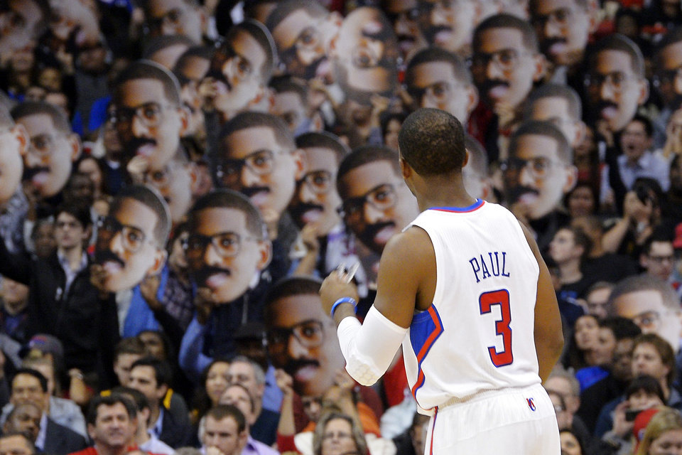 Los Angeles Clippers guard Chris Paul looks on as fans hold up pictures of him during the first half of their NBA basketball game against the Dallas Mavericks, Wednesday, Jan. 9, 2013, in Los Angeles. (AP Photo/Mark J. Terrill)