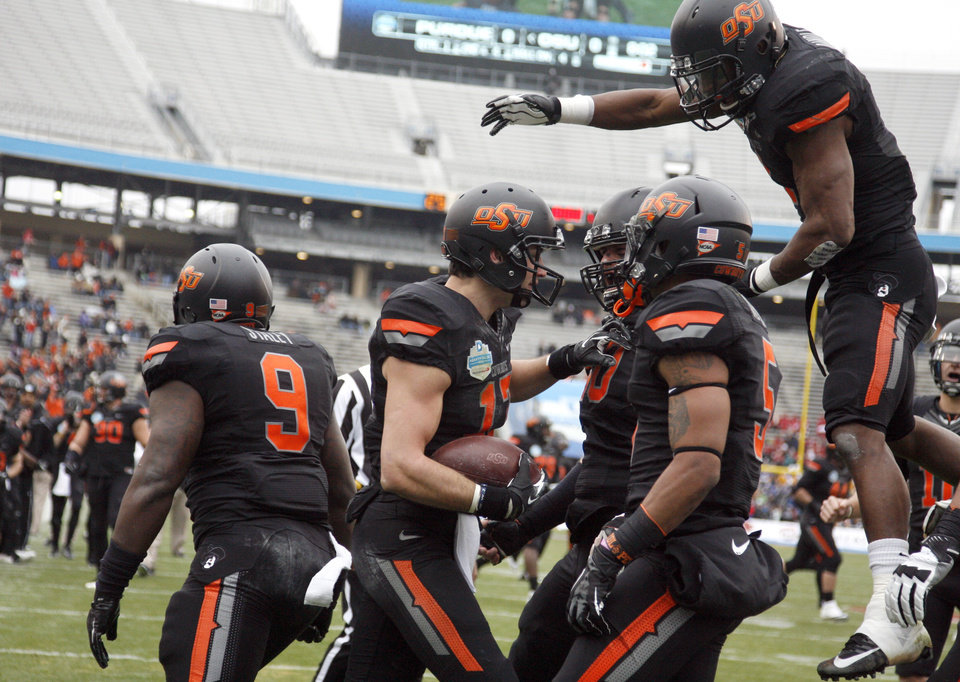 Photo - Oklahoma State celebrates a Charlie Moore (17) touchdown during the Heart of Dallas Bowl football game between the Oklahoma State University (OSU) and Purdue University at the Cotton Bowl in Dallas,  Tuesday,Jan. 1, 2013. Photo by Sarah Phipps, The Oklahoman