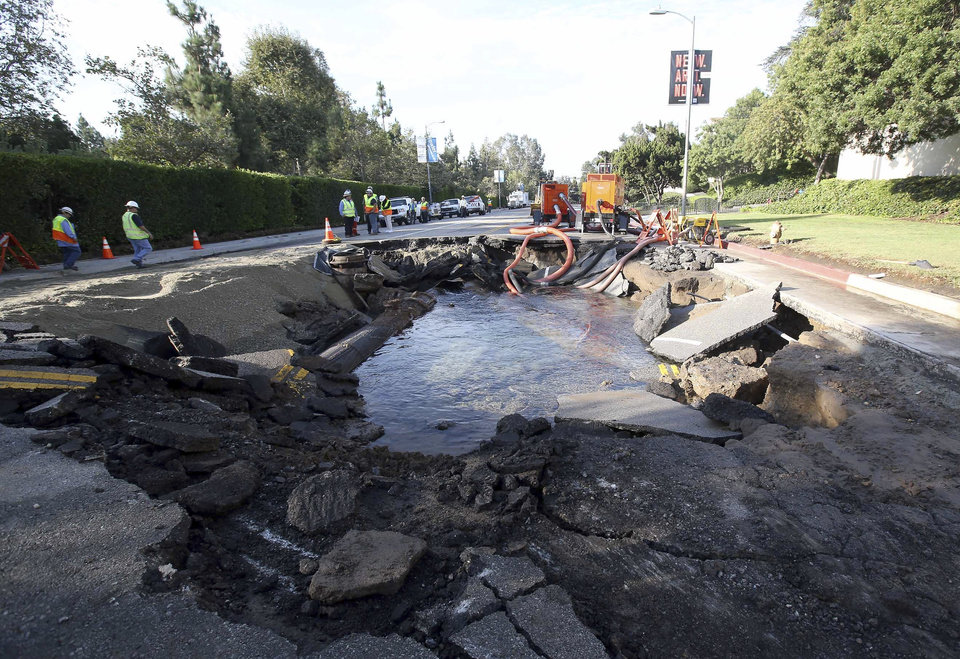 Photo - The site of a water main break is shown near UCLA Wednesday July 30, 2014, in Los Angeles. A ruptured 93-year-old water main on Tuesday left the UCLA campus awash in 8 million gallons of water in the middle of California's worst drought in decades, stranding people in parking garages and flooding the school's storied basketball court less than two years after a major renovation. (AP Photo/Nick Ut)