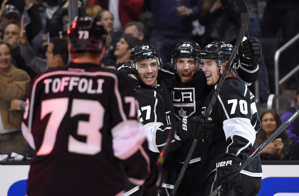 Photo - Los Angeles Kings center Jarret Stoll, second from right, celebrates his goal with center Tyler Toffoli, left, defenseman Alec Martinez, second from left, and left wing Tanner Pearson during the second period in Game 3 of an NHL hockey first-round playoff series against the San Jose Sharks, Tuesday, April 22, 2014, in Los Angeles. (AP Photo/Mark J. Terrill)