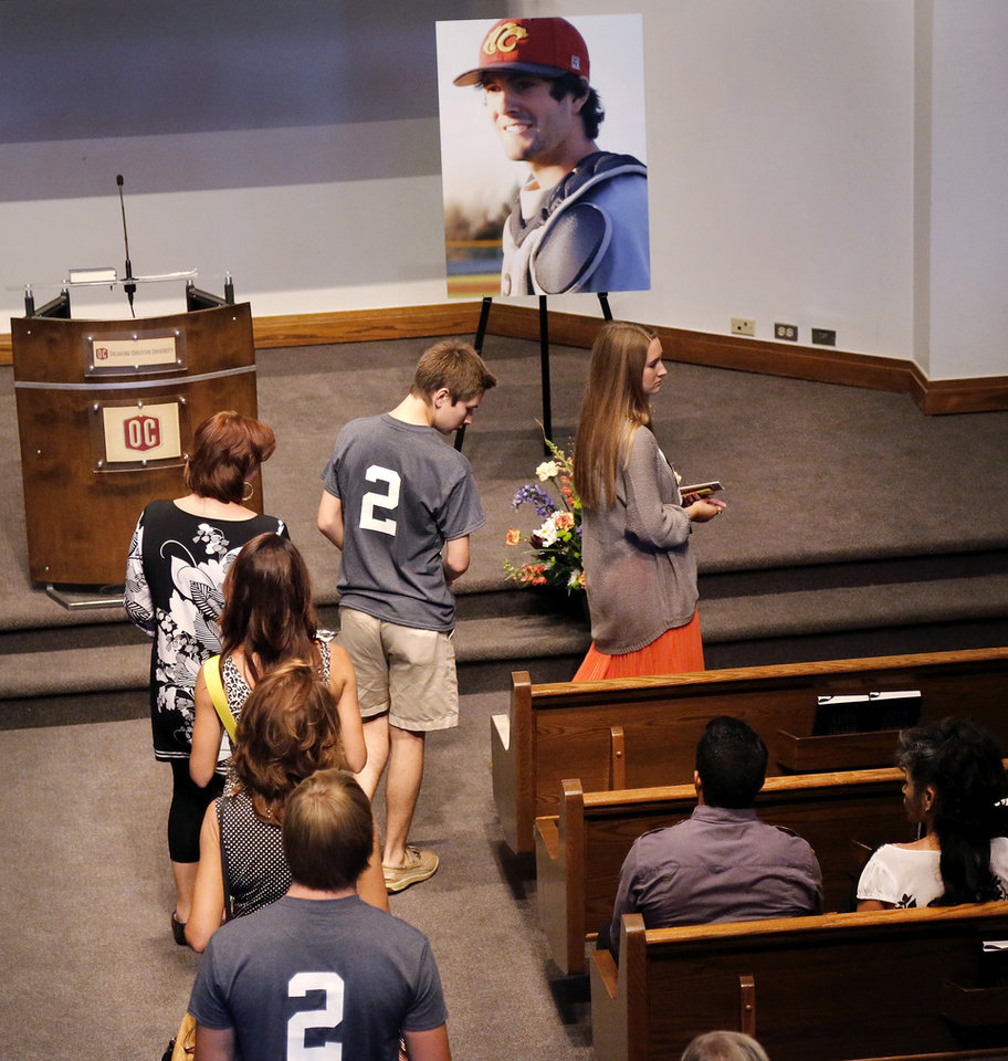 People file past a large portrait of Christopher Ryan Lane wearing his East Central University baseball uniform as they take their seats in a front pew before the service begins. Lane wore a jersey with the number 2 on it when he played at Redlands Community College in El Reno, Okla. About 200 friends, many of them former college baseball teammates, attended a memorial service at Oklahoma Christian University Saturday afternoon, Aug. 24, 2013, to remember student-athlete Christopher Lane during a memorial service for the East Central University athlete who was gunned down while jogging in Duncan, Okla. last week. Photo by Jim Beckel, The Oklahoman.