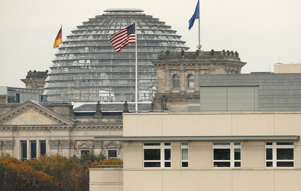 Photo - FILE - in this Oct. 25, 2013 file photo the American flag flies on top of the U.S. embassy in front of the  Reichstag building that houses the German Parliament, Bundestag, in Berlin, Germany. Germany took the dramatic step Thursday of asking the top U.S. intelligence official in Berlin to leave the country, following two reported cases of suspected U.S. spying and the yearlong spat over eavesdropping by the National Security Agency.