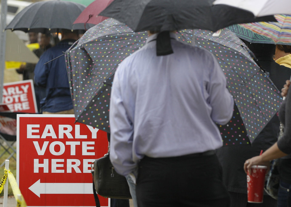 Photo -   Arkansas voters line up in the rain at an early voting poling place in Little Rock, Ark., Monday, Nov. 5, 2012, the last day to vote in advance in the Nov. 6, general election. (AP Photo/Danny Johnston)