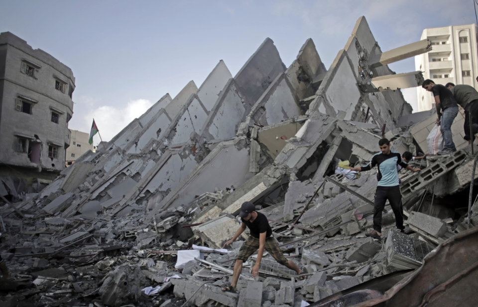 Photo - Palestinians salvage items from the rubble of the destroyed 15-story Basha Tower, following early morning Israeli airstrikes in Gaza City, Tuesday, Aug. 26, 2014. Israel bombed two Gaza City high-rises with dozens of homes and shops Tuesday, collapsing the 15-story Basha Tower and severely damaging the Italian Complex in a further escalation in seven weeks of cross-border fighting with Hamas. Both buildings were evacuated after receiving warnings of impending strikes. (AP Photo/Khalil Hamra)