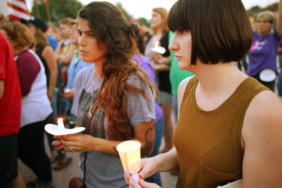 Photo - Michaela Slavid, left, and Liz Cobb hold candles during the Oklahoma Standing in Solidarity  with Charlottesville Rally at the Capitol Sunday, August 13, 2017. Photo by Doug Hoke, The Oklahoman