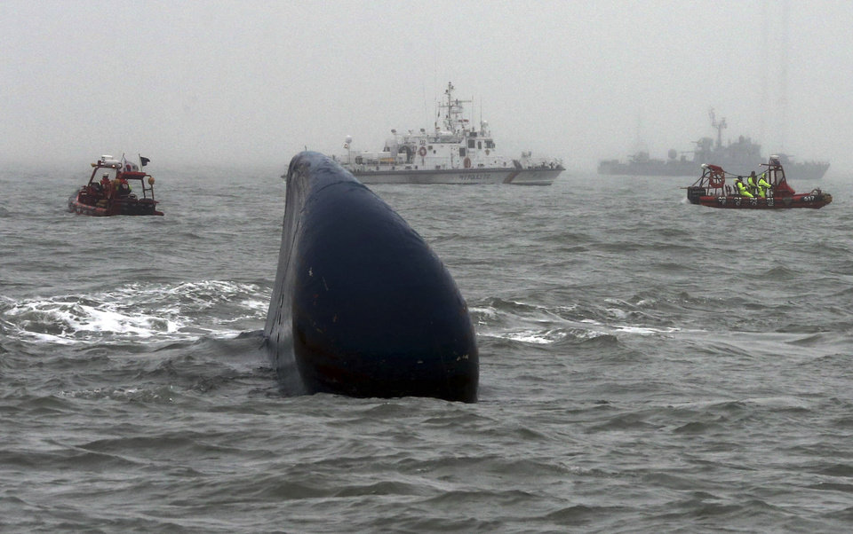 """Photo - FILE - In this April 18, 2014 file photo, South Korean Coast Guard officers search missing passengers aboard the ferry Sewol, center, in the water off the southern coast near Jindo, South Korea. The South Korean government is scrambling to fix what Prime Minister Park Geun-hye calls the """"deep-rooted evils"""" that contributed to last month's ferry sinking, which left more than 300 people dead or missing. As investigators probe cozy links between the shipping industry and its regulators, Seoul has promised new monitoring and regulations for domestic passenger ships, which are not governed by international rules. (AP Photo/Yonhap, File) KOREA OUT"""