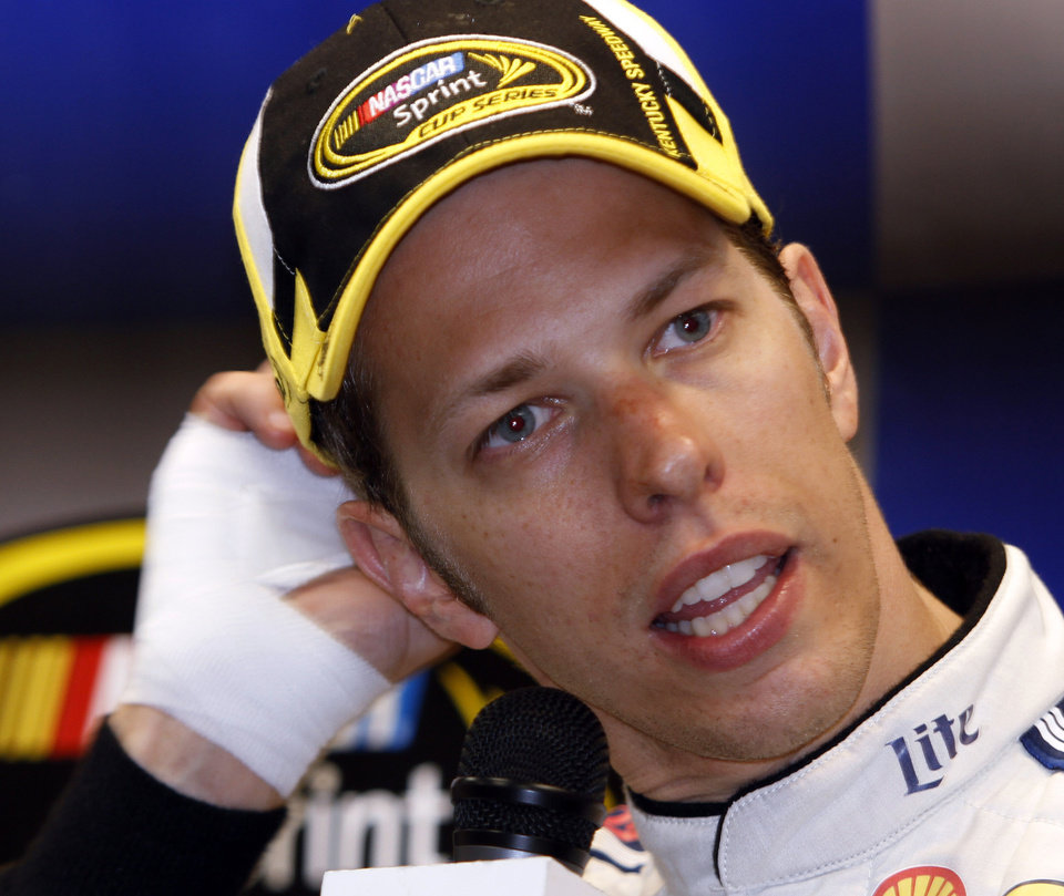 Photo - Brad Keselowski scratches his head with his bandaged hand at the news conference after the NASCAR Sprint Cup series auto race Saturday, June  28, 2014 at Kentucky Speedway in Sparta, Ky. Keselowski might need to be more mature in his victory celebrations, but the 30-year-old is definitely showing that he's growing up on the race track. Keselowski heads to Daytona showing flashes of the form that won the 2012 Sprint Cup Series championship, best demonstrated by Saturday's dominance at Kentucky Speedway.(AP Photo/James Crisp)