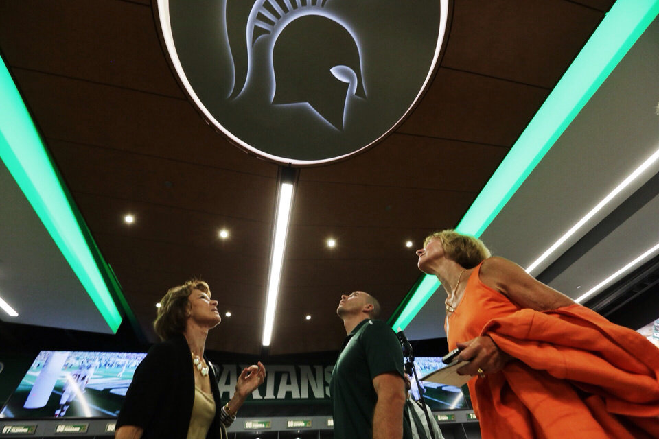 Photo - In this Monday, Aug. 25, 2014, photo, from left, Bonnie Knutson, of Lansing, Matt Warner, of East Lansing, and Sue Hansen, of Owosso, look up at a Michigan State University logo in the new home locker room during a tour of the new North End Zone Complex renovations at Spartan Stadium in East Lansing on the Michigan State Campus. (AP Photo/Detroit Free Press, Ryan Garza)  DETROIT NEWS OUT, TV OUT, INTERNET OUT, MAGS OUT, NO SALES, MANDATORY CREDIT DETROIT FREE PRESS