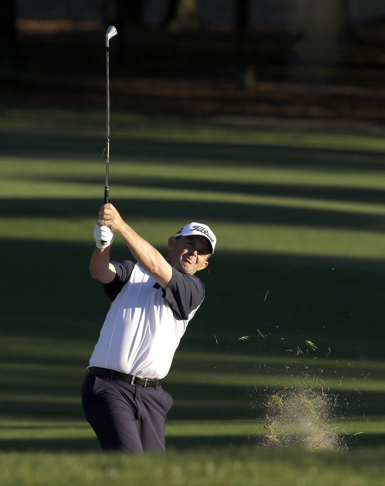 Photo - Greg Chalmers, of Australia, hits from the rough along the ninth fairway during the first round of the Valspar Championship golf tournament at Innisbrook on Thursday, March 13, 2014, in Palm Harbor, Fla. (AP Photo/Chris O'Meara)