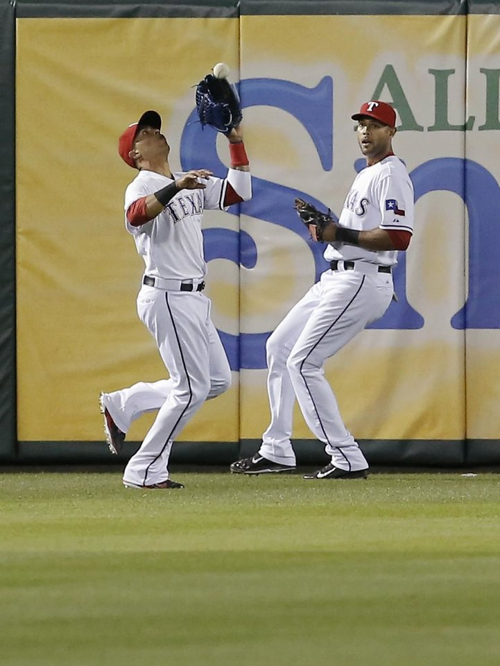 Photo - Texas Rangers right fielder Alex Rios, right, looks on as teammate and center fielder Leonys Martin catches a fly ball hit by Seattle Mariners' Justin Smoak during the ninth inning of a baseball game on Wednesday, April 16, 2014, in Arlington, Texas. Texas won 3-2. (AP Photo/Brandon Wade)