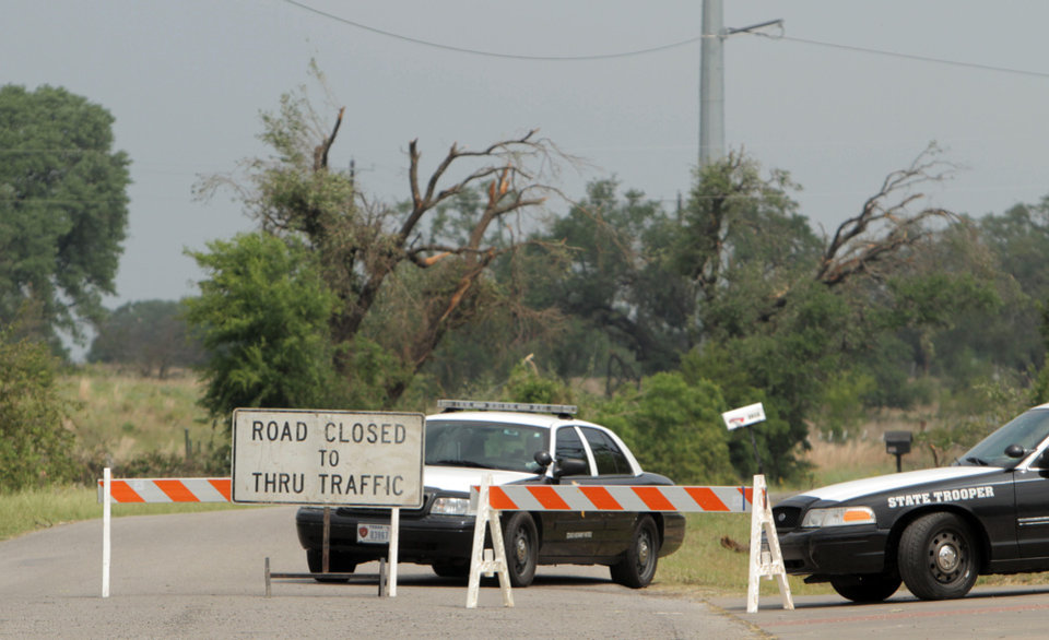 Photo - Texas State Troopers sit in front of a closed road due to storm damage in Granbury, Texas, Friday, May 17, 2013. On Wednesday an EF-4 tornado hit the small north Texas town. (AP Photo/Mike Fuentes)