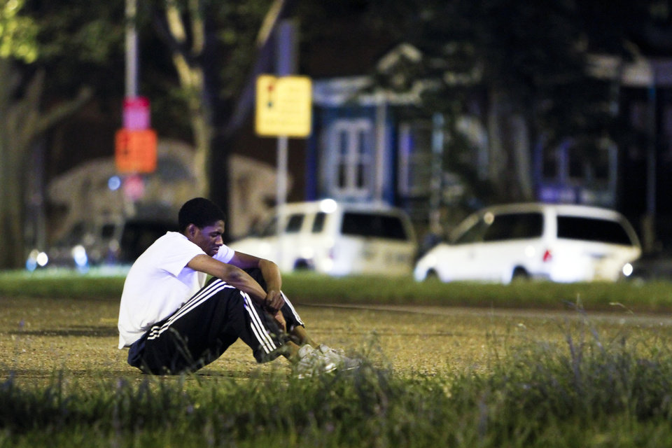 Photo - A man who identified himself as a cousin of the victim sits alone in the middle of the Roosevelt Boulevard near the scene of a fatal accident in the Olney section of Philadelphia on Tuesday July 16, 2013. Philadelphia police are investigating whether cars may have been drag racing when a mother and two young sons were struck and killed attempting to cross a busy highway. The woman's two other sons ages 4 and 5 are in critical condition. (AP Photo/ Joseph Kaczmarek)