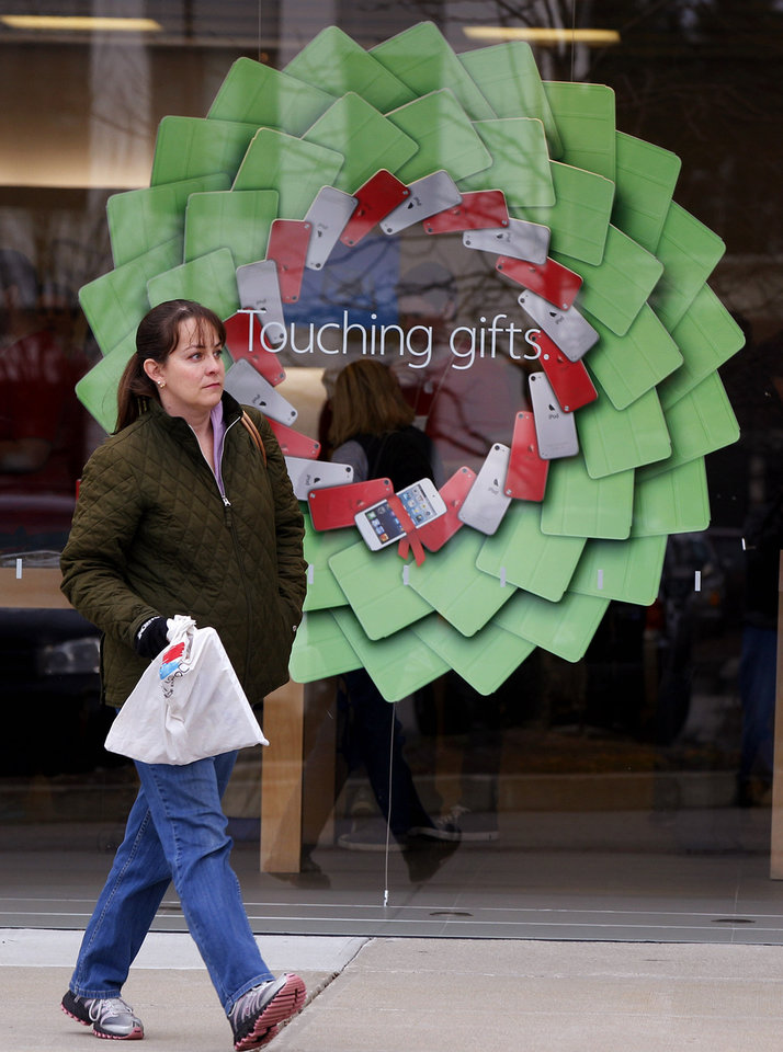 "Photo - A shopper carries a bag past a holiday display at the Apple Store at the Derby Street Shoppes in Hingham, Mass. Friday, Dec. 7, 2012. This holiday shopping season, stores haven't been offering the same big discounts as they did in previous years as they tried to lure shoppers in with other incentives,but during the final days leading up to Christmas, shoppers will see more of those jaw-dropping ""70 percent off"" sale signs as stores try to salvage a season that so far has been disappointing. (AP Photo/Stephan Savoia)"
