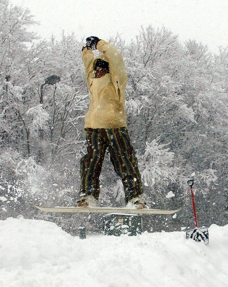 Photo - Greg Davis nails a 180-degree turn on a snow jump he build at Reservoir Park in Fort Wayne, Ind., Sunday, Jan 5, 2014. Several hours of light but steady snow brought out sledders and cautious drivers.   (AP Photo/The Journal-Gazette, Samuel Hoffman)  NEWS-SENTINEL OUT; MANDATORY CREDIT; NO SALES; MAGS OUT