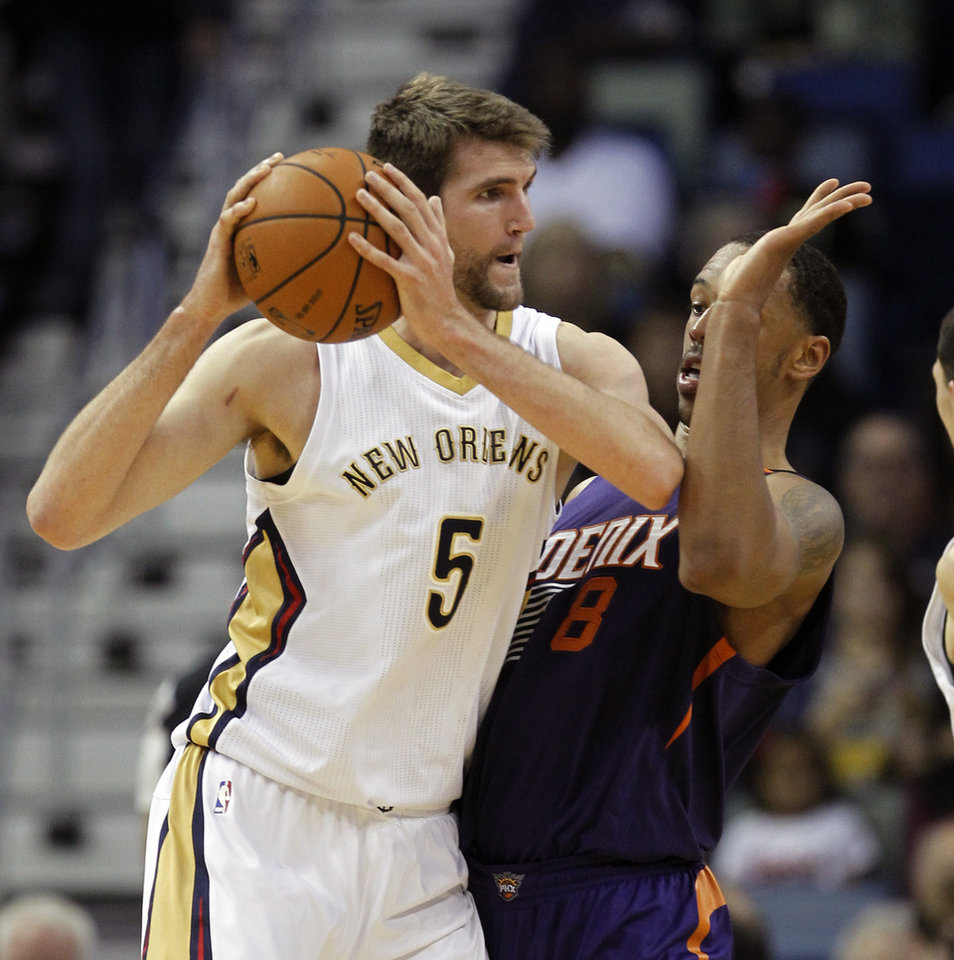 Photo - New Orleans Pelicans center Jeff Withey (5) tries to get around Phoenix Suns forward Channing Frye (8) in the first half of an NBA basketball game in New Orleans, Wednesday, April 9, 2014. (AP Photo/Bill Haber)