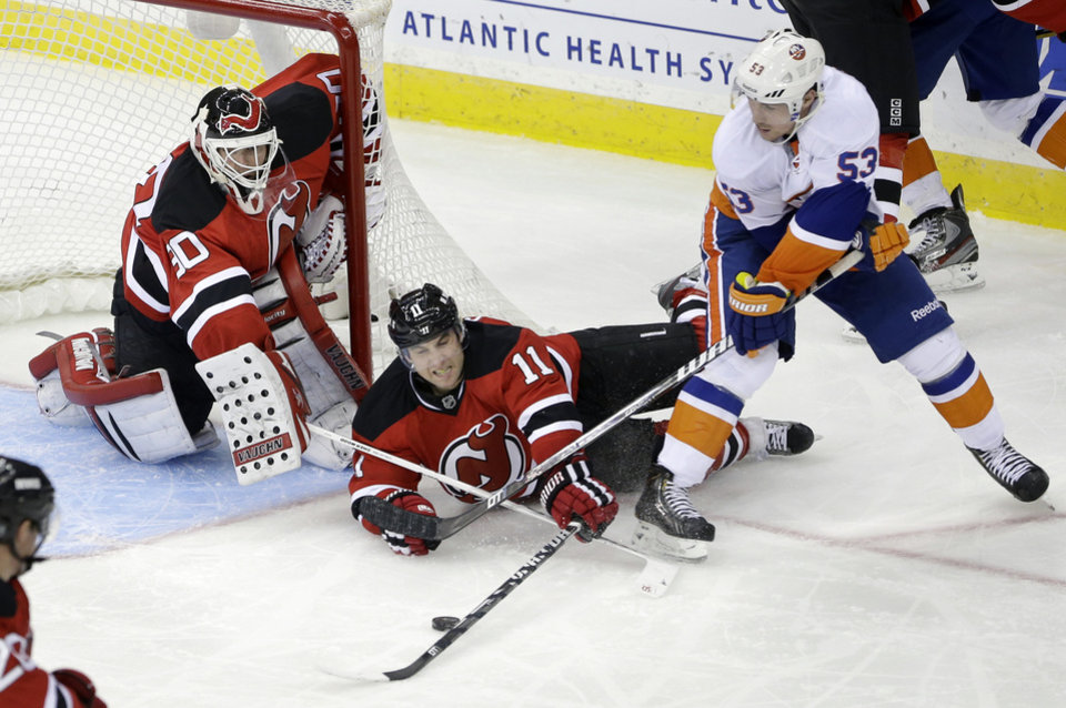 Photo - New Jersey Devils goalie Martin Brodeur (30) and Stephen Gionta (11) defend as New York Islanders' Casey Cizikas (53) tries to score a goal during the second period of an NHL hockey game Monday, April 1, 2013, in Newark, N.J. (AP Photo/Mel Evans)
