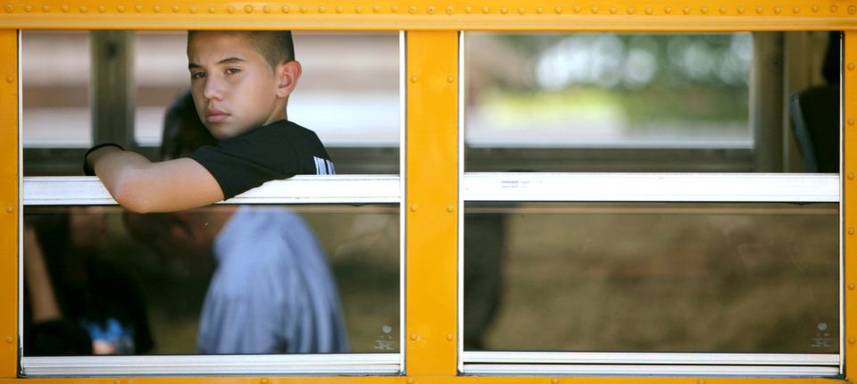 Photo - HEAT / HOT WEATHER / SCHOOL BUS: Luis Hernandez, an eighth-grader at Webster Middle School, waits for other students to board the bus outside Webster Middle School in Oklahoma City on Monday, Aug. 1, 2011. Photo by John Clanton, The Oklahoman ORG XMIT: KOD