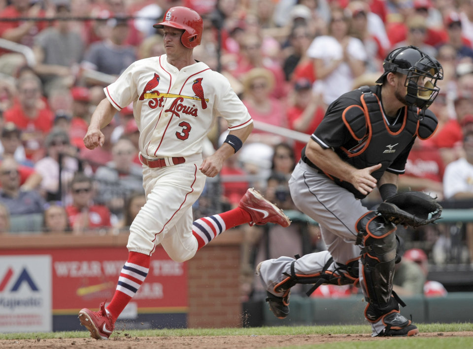Photo - St. Louis Cardinals' Mark Ellis (3) scores from second on a single by Matt Holliday as Miami Marlins catcher Jeff Mathis waits for a late throw in the fourth inning of a baseball game, Saturday, July 5, 2014 in St. Louis.(AP Photo/Tom Gannam)