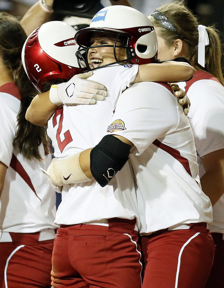 Photo - OU's Lauren Chamberlain (44), right, hugs Brianna Turang (2) after Chamberlain hit the game-winning home run to score them both in the twelfth inning during Game 1 of the Women's College World Series NCAA softball championship series between Oklahoma and Tennessee at ASA Hall of Fame Stadium in Oklahoma City, Monday, June 3, 2013. OU won 5-3 in 12 innings. Photo by Nate Billings, The Oklahoman