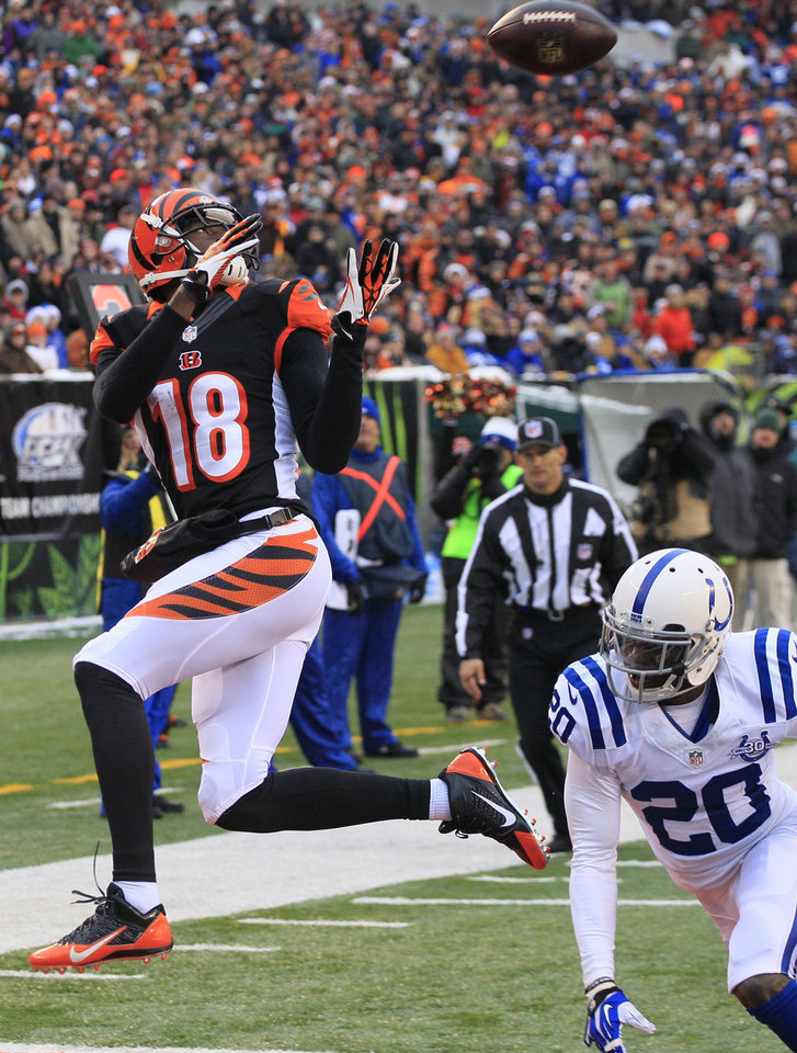 Photo - Cincinnati Bengals wide receiver A.J. Green (18) catches a 9-yard touchdown pass against Indianapolis Colts free safety Darius Butler (20) in the second half of an NFL football game, Sunday, Dec. 8, 2013, in Cincinnati. (AP Photo/Tom Uhlman)