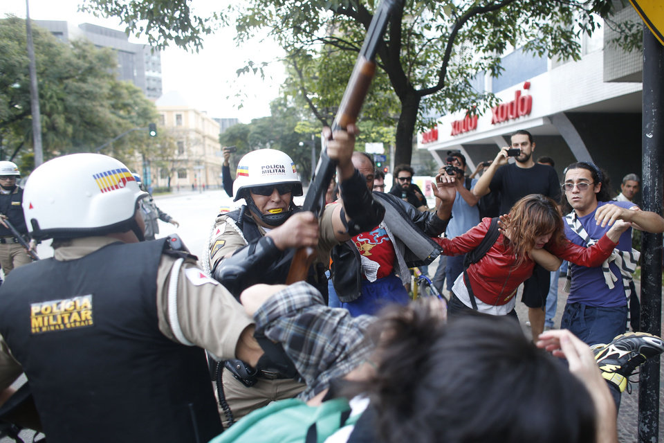 Photo - A policeman hits demonstrators with a shotgun during a protest against the 2014 World Cup in Belo Horizonte, Brazil, Thursday, June, 12, 2014. Demonstrators gathered in downtown Belo Horizonte to protest against the 2014 World Cup soccer tournament. (AP Photo/Victor R. Caivano)