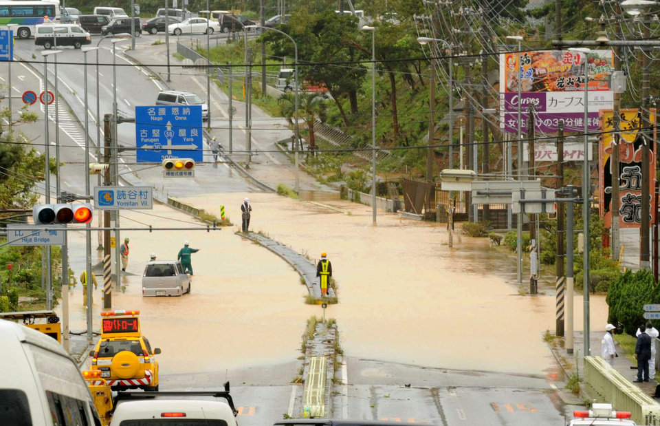 Photo - A road is submerged by an overflowed river following a typhoon in Yomitan, Okinawa, Wednesday, July 9, 2014. A powerful storm slammed through the southwestern Japanese island of Okinawa, leaving at least 28 people injured and 63,000 homes without power before swerving toward the bigger island of Kyushu on Wednesday. (AP Photo/Ryukyu Shimpo via Kyodo News) JAPAN OUT, NO SALES, NO ARCHIVE, MANDATORY CREDIT