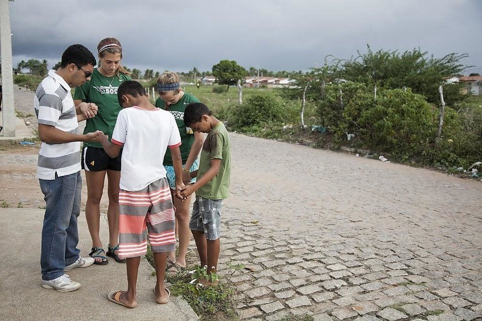 Photo -  With the help of a Brazilian Baptist translator, Allie Preston, second from left, and Kenzi Bice — players on Oklahoma Baptist University women's soccer team — pray with two Brazilian boys after telling them the story of Jesus during an evangelism trip to Brazil before the FIFA World Cup. Photo provided by Southern Baptist Convention's International Mission Board