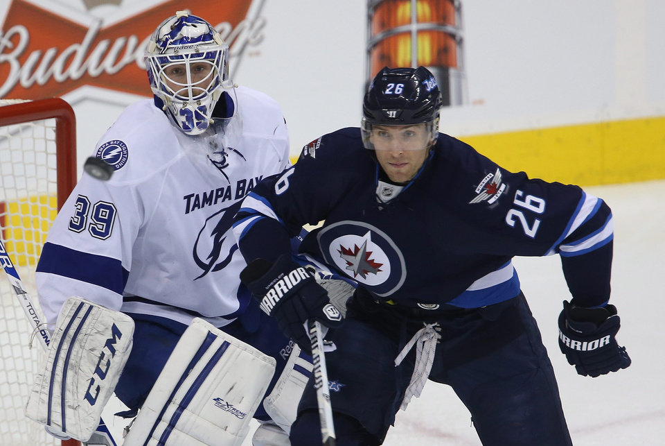 Photo - Tampa Bay Lightning goaltender Anders Lindback (39) and Winnipeg Jets' Blake Wheeler (26) watch a flying puck during the first period of an NHL hockey game Tuesday, Jan. 7, 2014, in Winnipeg, Manitoba. (AP Photo/The Canadian Press, Trevor Hagan)