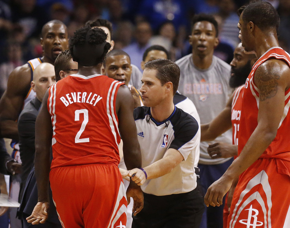 Photo - Official David Guthrie, center, holds back Houston Rockets guard Pat Beverley (2) from Oklahoma City Thunder guard Russell Westbrook, between Guthrie and Beverley, during the first quarter of an NBA basketball game in Oklahoma City, Tuesday, March 11, 2014. (AP Photo/Sue Ogrocki)
