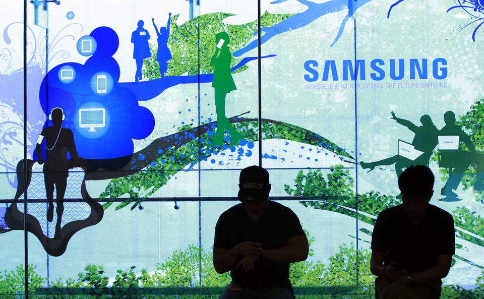 Photo - People stand in front of a Samsung Electronics Co's showroom in Seoul, South Korea, Thursday, July 31, 2014. Samsung Electronics Co. reported a bigger-than-expected fall in second quarter profit on Thursday and said it was uncertain if earnings from its handset business would improve in the current quarter.(AP Photo/Ahn Young-joon)