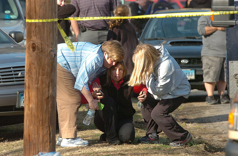 People are comforted near Sandy Hook Elementary School, Friday, Dec. 14, 2012 in Newtown, Conn. A man killed his mother at home and then opened fire Friday inside the elementary school where she taught, massacring 26 people, including 20 children, as youngsters cowered in fear to the sound of gunshots echoing through the building and screams coming over the intercom. (AP Photo/The Hour, Alex von Kleydorff)