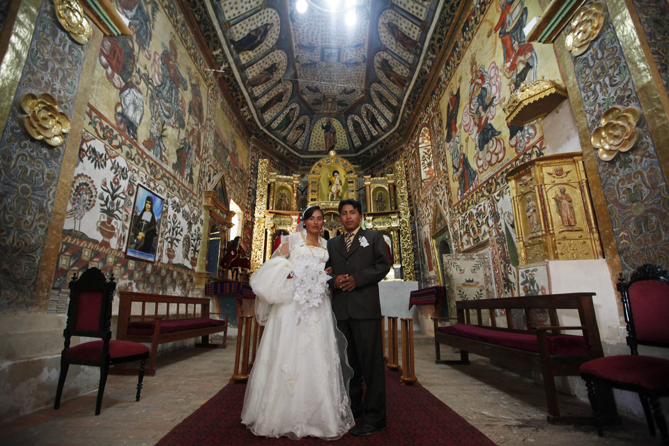 A couple poses for pictures after their wedding inside the Sistine Chapel of Los Andes in Curahuara de Carangas, Oruro department, 260 km. (160 miles) south from La Paz, Bolivia, Saturday, Dec. 8, 2012. The colonial-era house of worship known in Bolivia as the Sistine Chapel of the Andes, built in 1608 to evangelize indigenous Bolivians into the Roman Catholic faith, was filled with flowers over the weekend for those celebrating two weddings and seven baptisms on the wind swept mountain plateau. (AP Photo/Juan Karita)